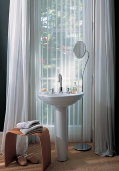 Pedestal sink in front of full-length window with white long bathroom curtains. Kathroom window coverings, bathroom window covering ideas.